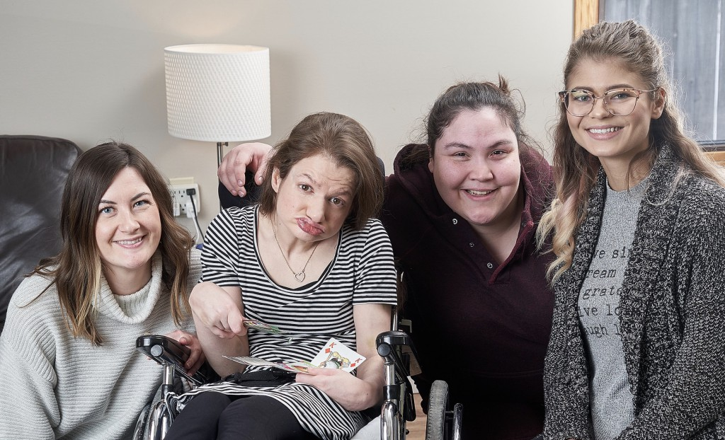 three women next to a woman in a wheelchair in a home.
